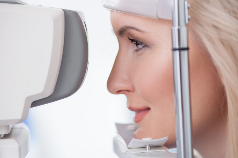 Cheerful blond girl is looking into eye test machine with concentration in oculist lab. She is smiling